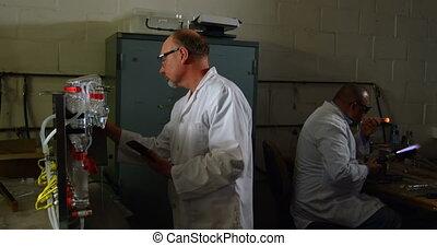 Caucasian male worker working on digital tablet in glass ...