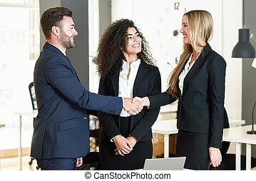 Caucasian man and woman shaking hands wearing suit.
