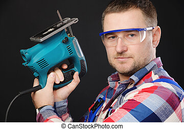Caucasian man builder carpenter in a shirt and overalls with an electric tool in his hands. Studio portrait of friendly artisan businessman