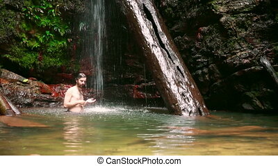 caucasian man enjoying in waterfall