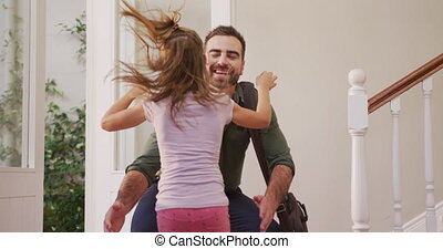 Caucasian man entering the front door of his house, greeting and embracing his daughter, in slow motion.