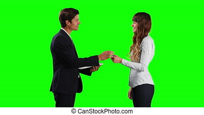 Side view of a Caucasian male sales advisor holding a file, giving car keys to a Caucasian female lessor, smiling and shaking hands, on green screen background