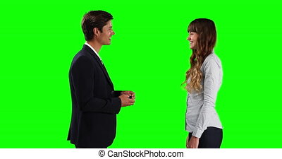 Side view of a Caucasian male sales advisor giving car keys to a Caucasian female lessor, smiling and shaking hands, on green screen background.