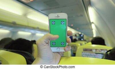 Caucasian Man Holding Smart Phone Inside Plane