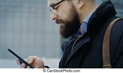 Caucasian man in glasses uses smartphone on the street