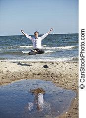 caucasian man in lotos pose levitates above the beach - ...