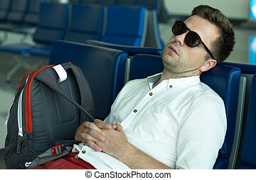 Caucasian man is sleeping in lounge area at the airport.