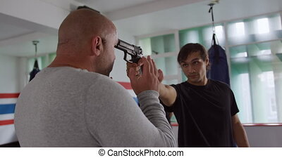 Caucasian man learning self defense from trainer in gym - ...