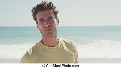Caucasian man looking at the camera at beach - Front view of...