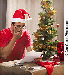 Caucasian man looking at the disastrous Xmas budget and ...