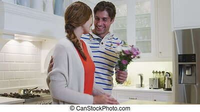Caucasian man offering flowers to his wife