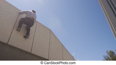 Caucasian man wearing casual clothes, practicing parkour in the city streets on a sunny day, climbing the wall and jumping down, in slow motion.