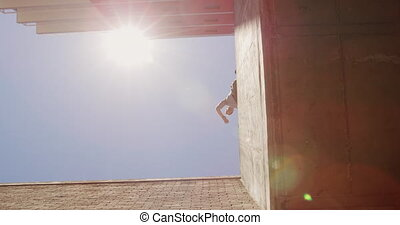 Caucasian man wearing casual clothes, practicing parkour in the city streets on a sunny day, jumping on handrails of the bridge, in slow motion.