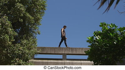 Caucasian man wearing casual clothes, practicing parkour in the city streets on a sunny day, walking on the edge of a bridge handrail, in slow motion.