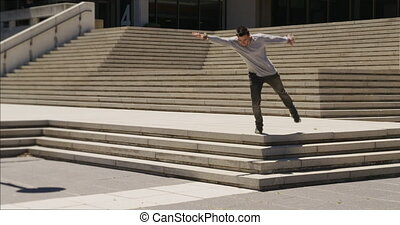 Caucasian man wearing casual clothes, practicing parkour in the city streets on a sunny day, doing a somersault while jumping from stairs, in slow motion.