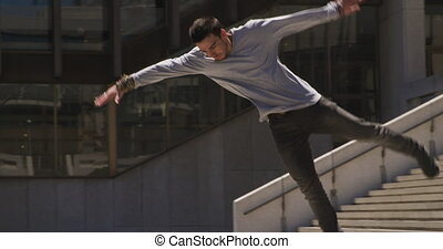 Caucasian man wearing casual clothes, practicing parkour in the city streets on a sunny day, doing a somersault, in slow motion.