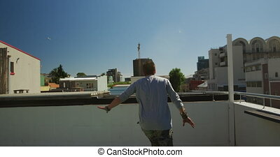 Caucasian man, wearing casual clothes, practicing parkour on a rooftop in a city on a sunny day, running and jumping, in slow motion.