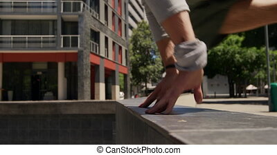 Mid section of a Caucasian man wearing casual clothes, practicing parkour in the city streets on a sunny day, jumping over the wall, in slow motion.