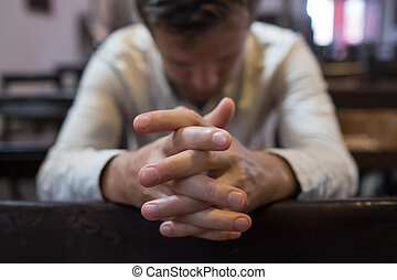 caucasian man praying in church. He has problems and ask God for help