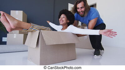 Caucasian man pushing his wife sitting in cardboard boxes at new apartment house