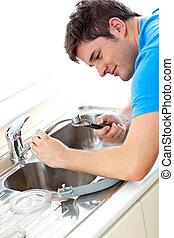 Caucasian man repairing a kitchen sink at home