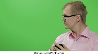 Caucasian man scrolling, texting on the smartphone. Place...