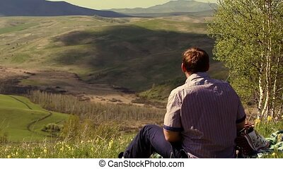 Caucasian man sitting in the mountains and enjoy the beauty of nature