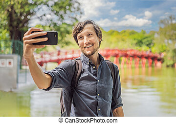Caucasian man traveler on background of Red Bridge in public park garden with trees and reflection in the middle of Hoan Kiem Lake in Downtown Hanoi. Vietnam reopens after coronavirus quarantine COVID 19