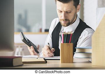 Caucasian man using calculator