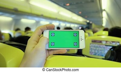 Caucasian Man Using Smart Phone App Inside Plane