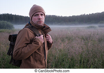 man walking through a field in summer at the evening.