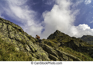 Caucasian man with backpack hiking on a trail in the rocky mountains