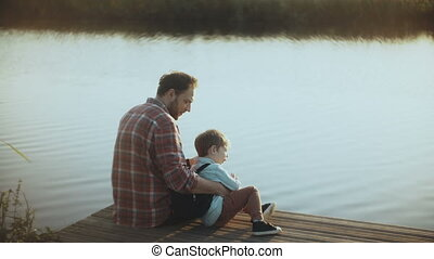 Caucasian man with little boy sit on a lake pier. Father and...
