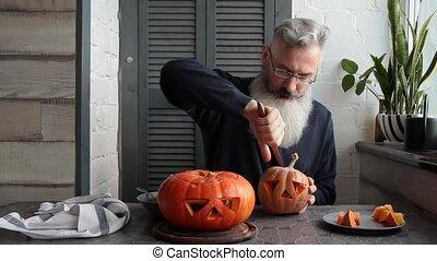Caucasian mature bearded man makes pumpkin lantern Jack-o-...