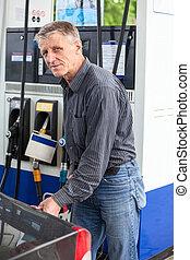 Caucasian mature man refueling car with gasoline