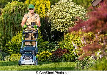 Caucasian Men Mowing Grass in His Garden