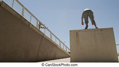 Two Caucasian men wearing casual clothes, practicing parkour in the city streets on a sunny day, jumping on the handrail of the bridge, in slow motion.