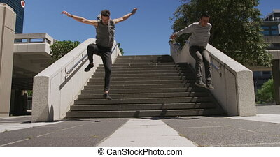 Two Caucasian men wearing casual clothes, practicing parkour in the city streets on a sunny day, doing a somersault while jumping from stairs, in slow motion.