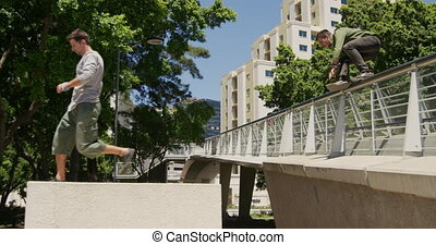 Two Caucasian men wearing casual clothes, practicing parkour in the city streets on a sunny day, jumping on handrails of the bridge, in slow motion.