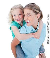 Caucasian mother giving her daughter piggyback ride