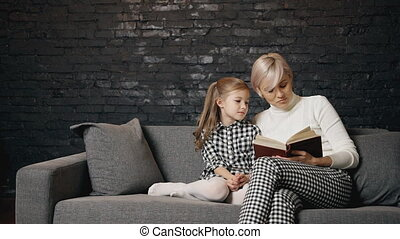 Caucasian mother is hugging beloved daughter and reading her...