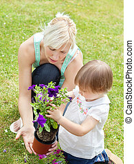 Caucasian Mother showing her daughter a purple flower