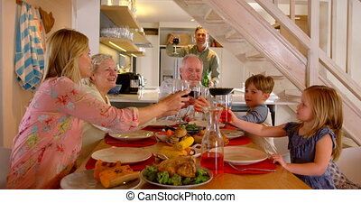 Caucasian multi-generation family toasting glasses of drinks on dining table at home 4k