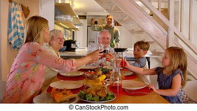 Caucasian multi-generation family toasting glasses of drinks...