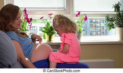 Caucasian pregnant woman and cute blond daughter girl playing with belly at home