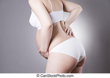 Caucasian pregnant woman in white lingerie with abdominal pain on gray studio background