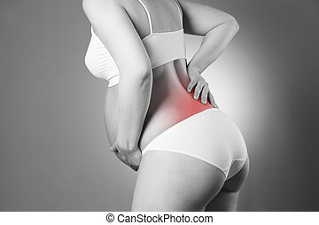 Caucasian pregnant woman in white lingerie with back pain on gray studio background