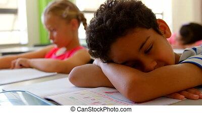 Caucasian schoolboy sleeping at desk in classroom at school 4k