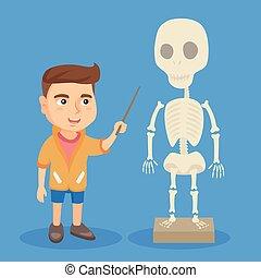 Caucasian schoolboy studying the human skeleton. - Little...