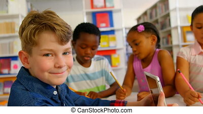 Side view of Caucasian schoolboy using digital tablet in school library. Schoolkids doing their classwork in the backgound 4k